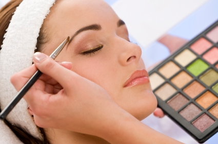 A beautiful young woman having her make up applied by a beautician in health spa.